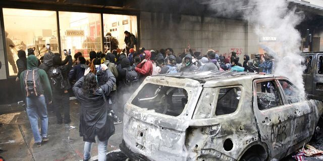 Looters storm a Nordstrom store near a torched police vehicle during a riot in Seattle, May 30, 2020. (Getty Images)