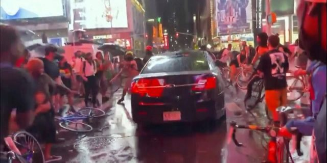 In this frame grab from a video by @datainput from the New York City Police Department Twitter account, a car moves through protesters, in New York's Times Square on Thursday. The New York Police Department says it is trying to find the car that drove through a group of Black Lives Matter protesters blocking a street in Times Square. (New York City Police Dept. via AP)