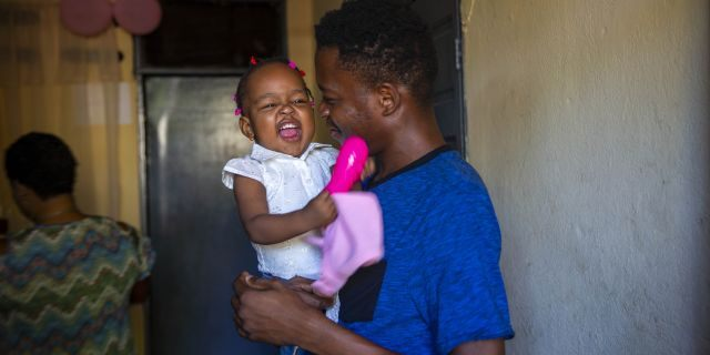 A man holds up his 1-year-old daughter at his house in Port-au-Prince, Haiti, Tuesday, Aug. 25, 2020. (Associated Press)
