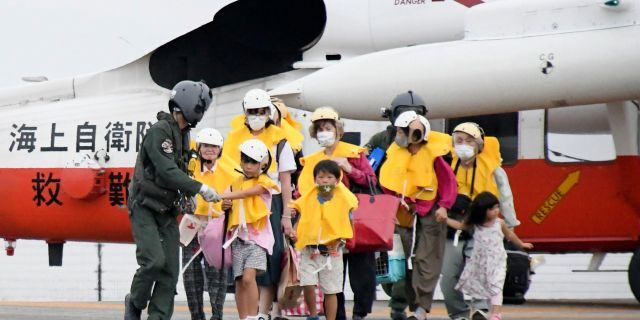 People arrive at a heliport in Kagoshima, in southern Japan, on Friday, Sept. 4, 2020, to take refuge ahead of a powerful typhoon. (Kyodo News via AP)