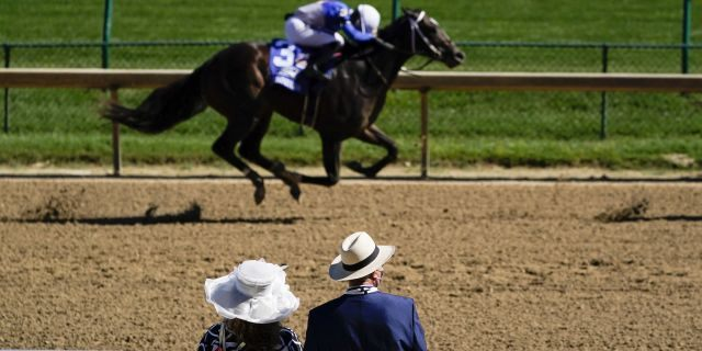 A couple watch a race before the 146th running of the Kentucky Derby at Churchill Downs, Sept. 5, in Louisville, Ky. (AP Photo/Charlie Riedel)