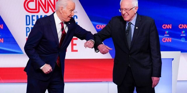 Former Vice President Joe Biden and Sen. Bernie Sanders greet one another before they participate in a Democratic presidential primary debate at CNN Studios in Washington. March 15, 2020. (AP Photo/Evan Vucci, File)