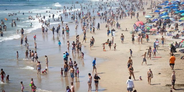 People are seen at the beach during a heat wave, Sunday, Sept. 6, 2020, in Huntington Beach, Calif. (AP Photo/Christian Monterrosa)