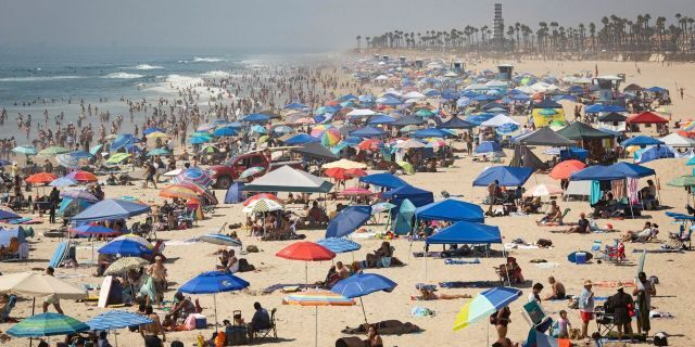 People escape the California heat wave at the beach, Sunday, Sept. 6, 2020, in Huntington Beach, Calif.