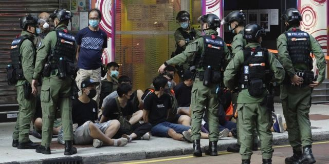 People sitting on the ground are arrested by police officers at a downtown street in Hong Kong Sunday, Sept. 6, 2020. (AP Photo/Vincent Yu)