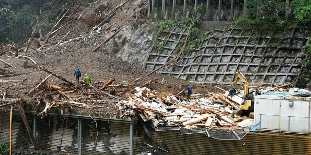 Rescuers work at a landslide site as a typhoon hit Shiiba village, Miyazaki prefecture, southwestern Japan Monday, Sept. 7, 2020.