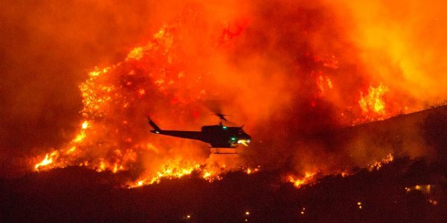 In this Saturday, Sept. 5, 2020, file photo, a helicopter prepares to drop water at a wildfire in Yucaipa, Calif.