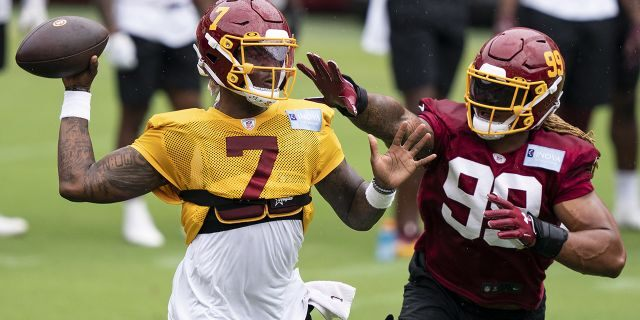 Washington quarterback Dwayne Haskins Jr. (7) passes under pressure from defensive end Chase Young (99) during an NFL football practice at FedEx Field, Monday, Aug. 31, 2020, in Washington. (AP Photo/Alex Brandon)