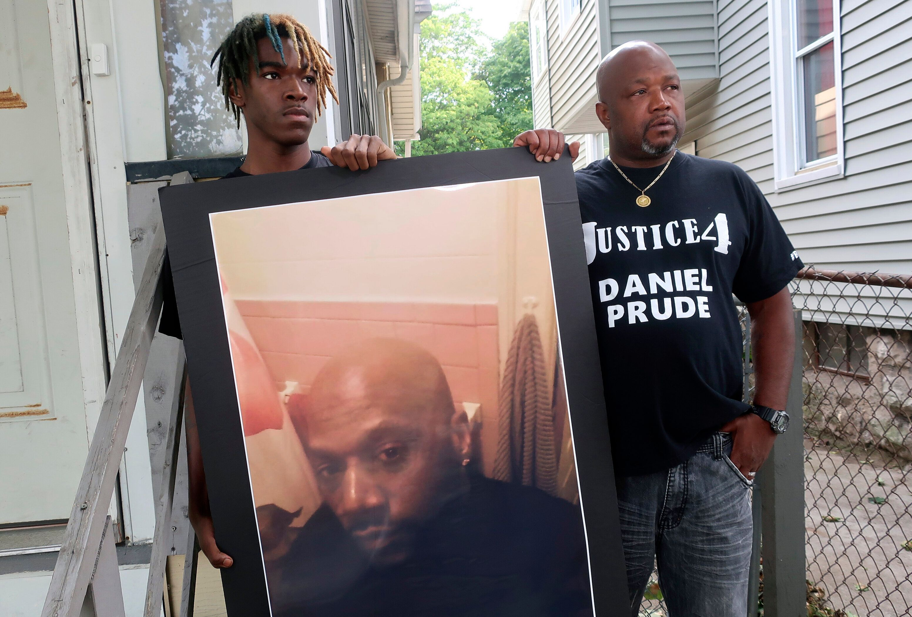 Joe Prude, uncle of Daniel Prude, right, and Daniel's nephew Armin, stand with a picture of Daniel Prude in Rochester, N.Y.,