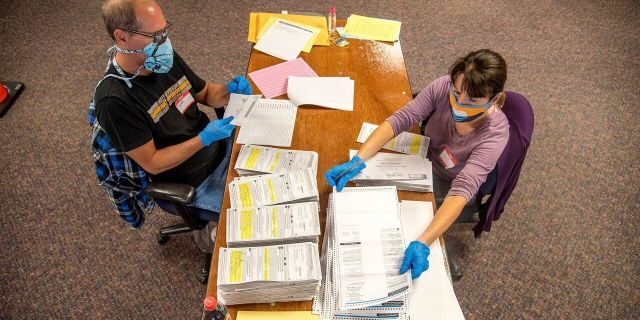 In this photo provided by Wisconsin Watch, election workers Jeff and Lori Lutzka, right, process absentee ballots at Milwaukee's central count facility on Aug. 11, 2020. (Will Cioci/Wisconsin Watch via AP)