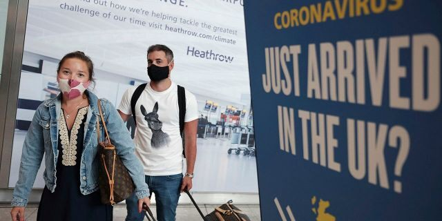 Passengers Charlotte and Frank, arrive at Heathrow Airport as they return from Mykonos in Greece, after the British Government added the island to the coronavirus quarantine list, at Heathrow, London, Tuesday Sept. 8, 2020. (Yui Mok/PA via AP)
