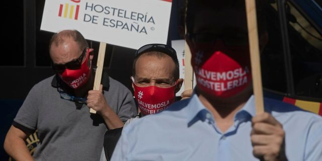 Bar and restaurant owners and workers protest against Covid-19 related restrictions in their sector in Madrid, Spain, Wednesday, Sept. 9, 2020. The Spanish capital, Madrid, has emerged as the most worrying source of new infections and regional authorities had announced new restrictions on social and family gatherings. Signs read 'Spanish hospitality industry'. (AP Photo/Paul White)
