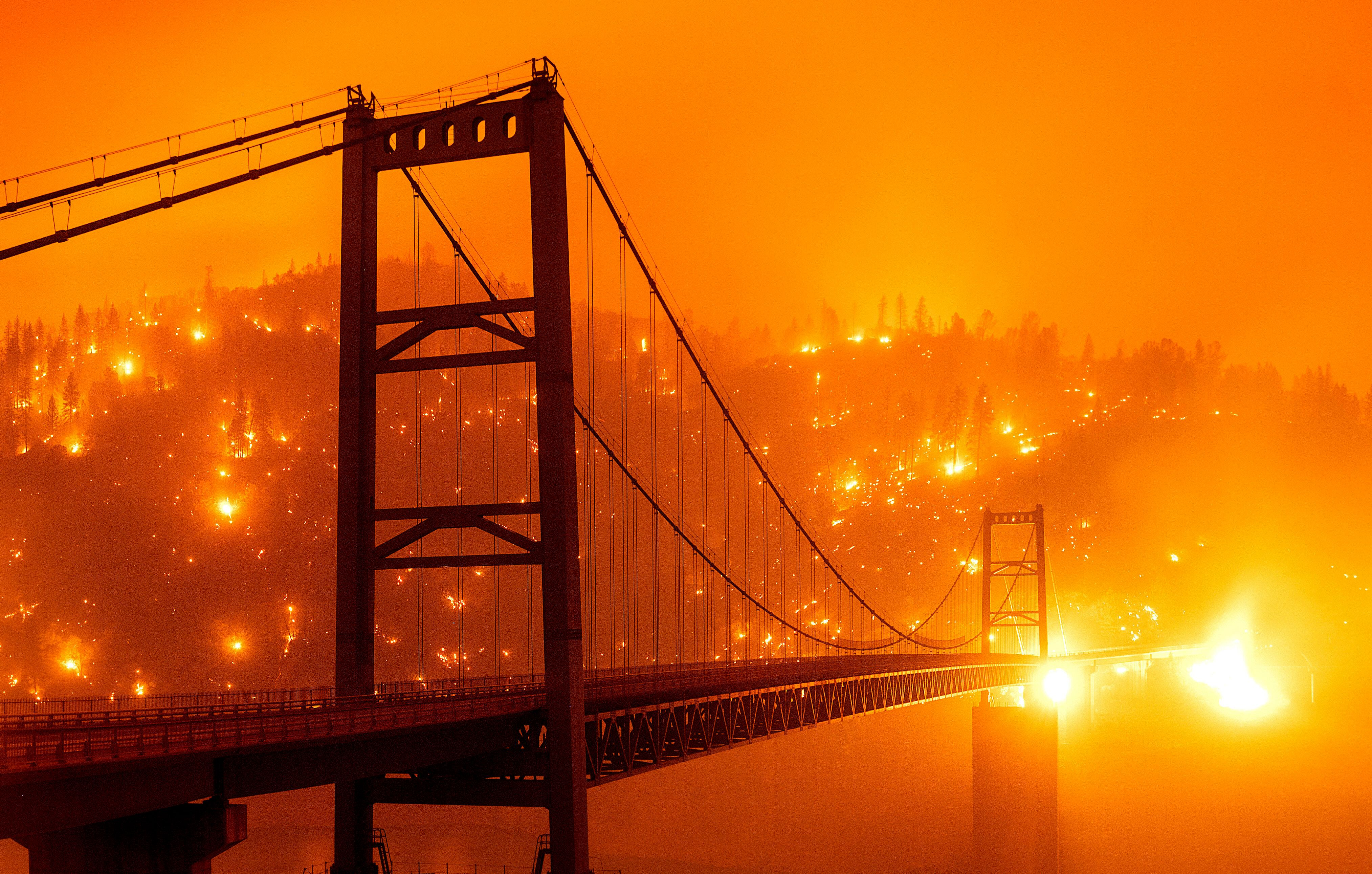 Embers light up a hillside behind the Bidwell Bar Bridge in Oroville, California.