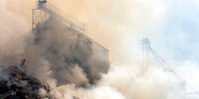 Grain from a collapsed grain elevator burns on Tuesday, Aug. 8, 2020, in Pine City, Wash. The grain elevator collapsed when a wildfire swept through town on Monday.