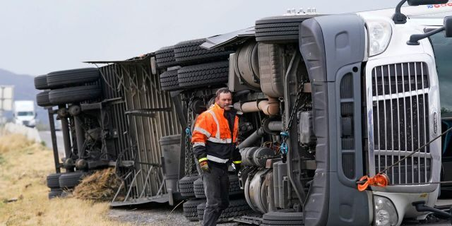 A semi rests on its side after after high winds toppled it on Interstate 15 Tuesday, Sept. 8, 2020, near Bountiful, Utah.