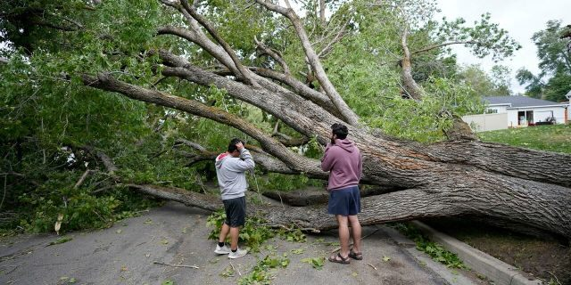People survey the damage after high winds caused widespread damage and power outages Tuesday, Sept. 8, 2020, in Salt Lake City.