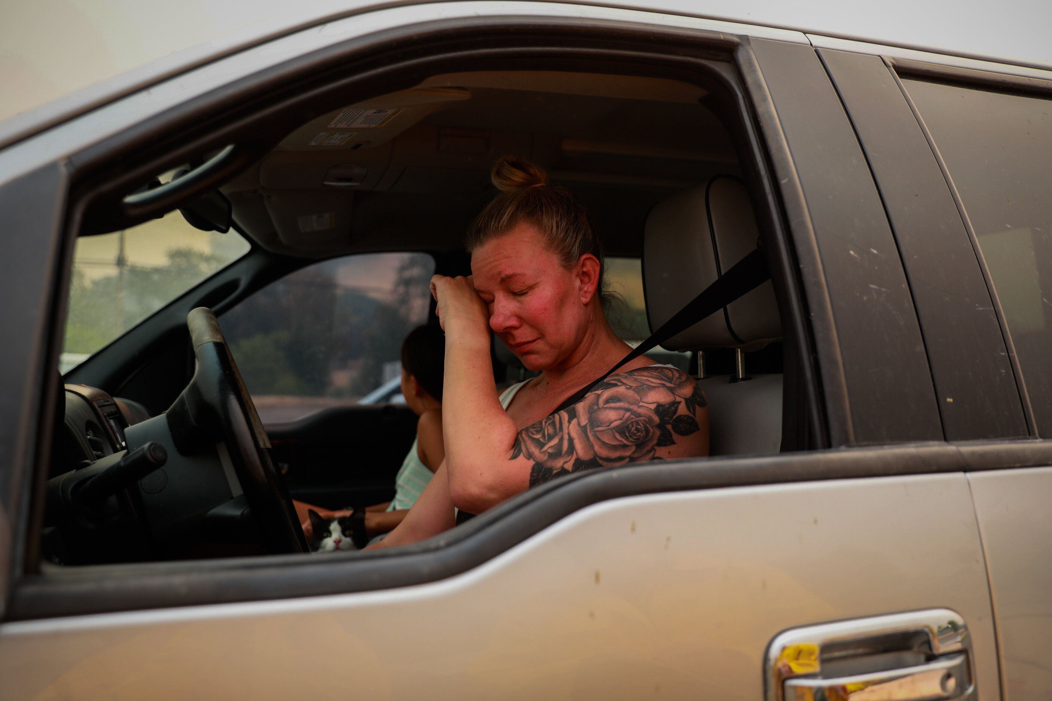 Gina Santos cries in her car after evacuating due to the LNU Lightning Complex Fire in Vacaville, California, on Aug. 19, 202