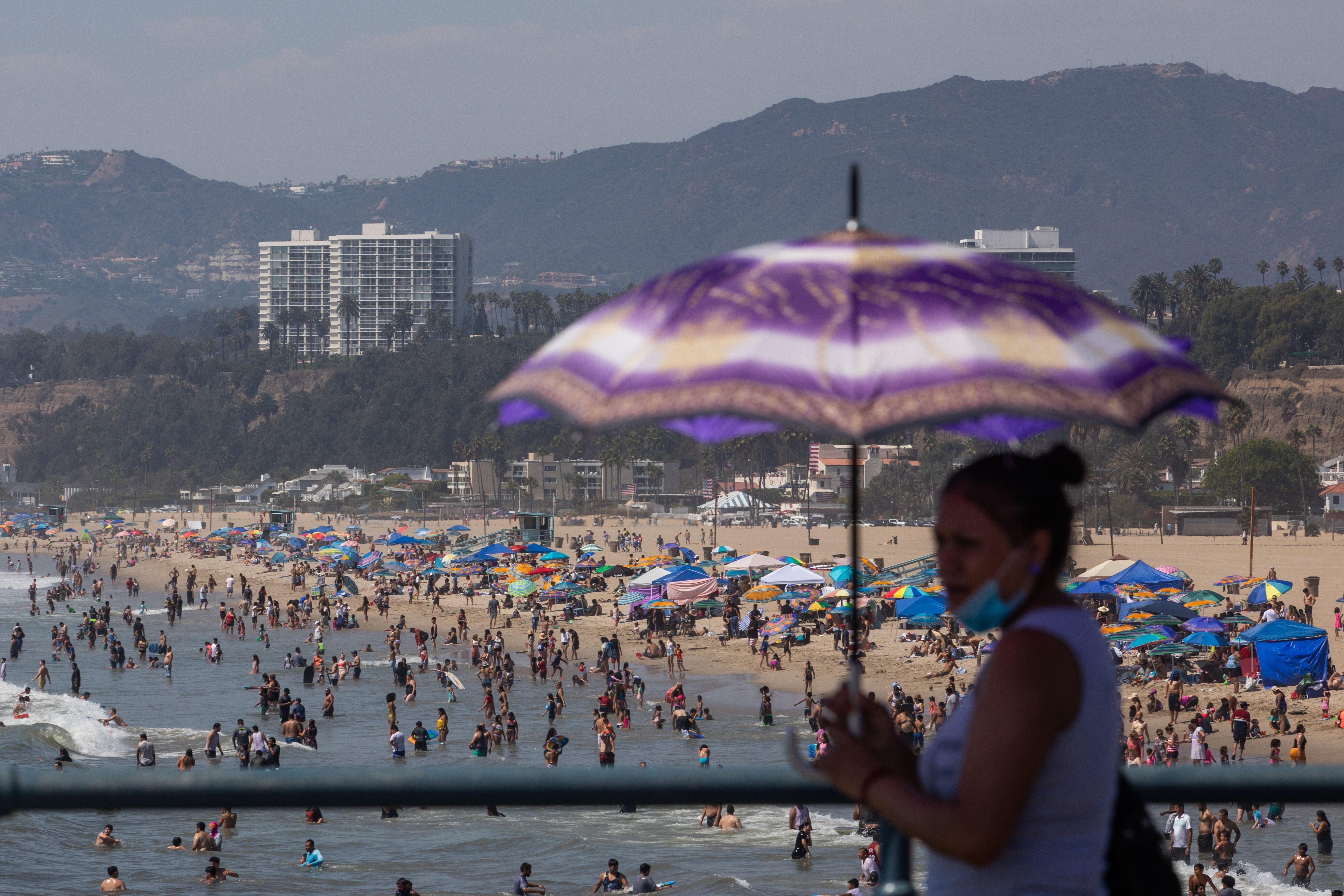 A woman uses an umbrella to protect herself from the sun at Santa Monica pier while people flocked to the beach amid a heat w