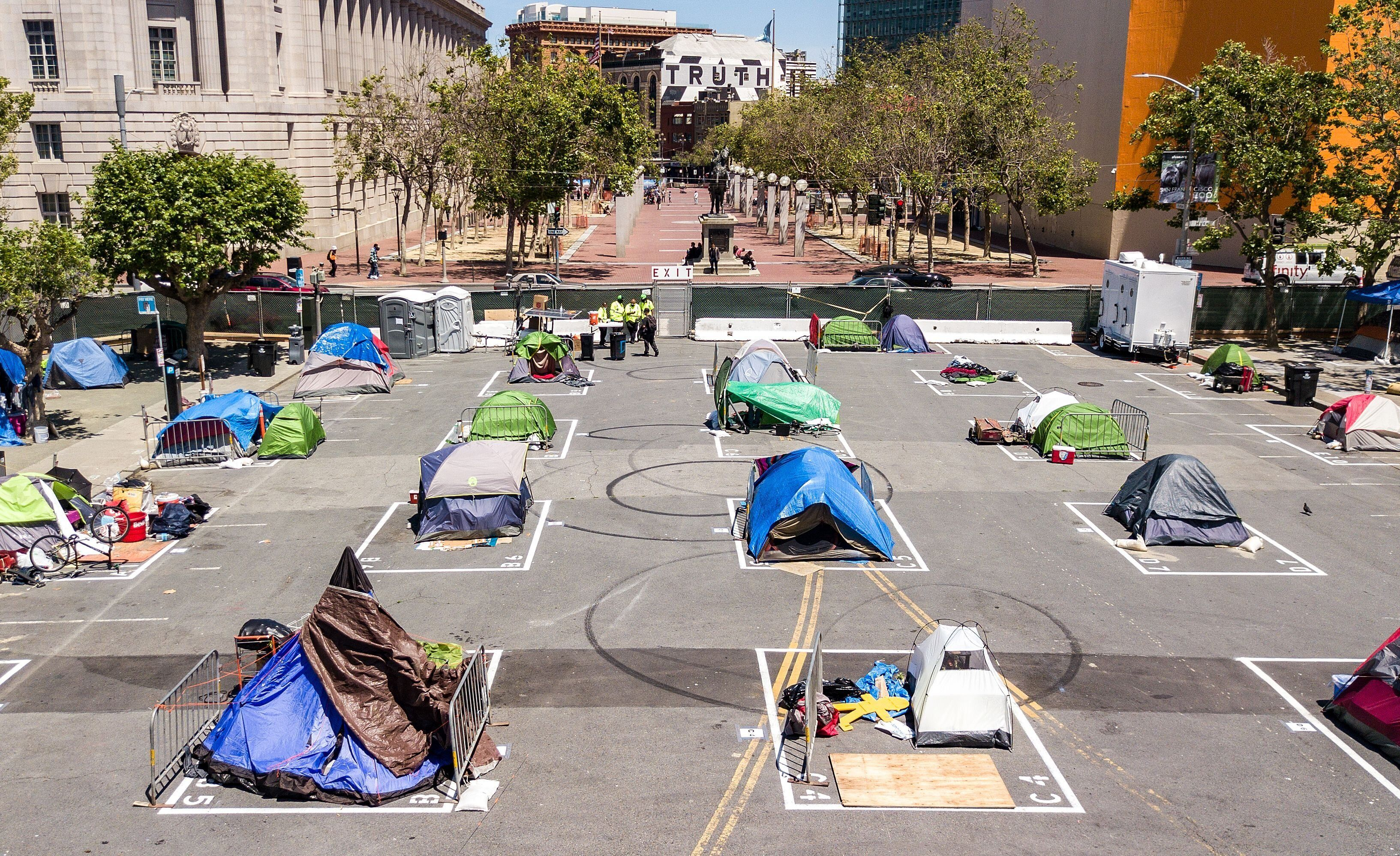 Rectangles on the ground encourage homeless people to observe social distancing at a city-sanctioned homeless encampment acro