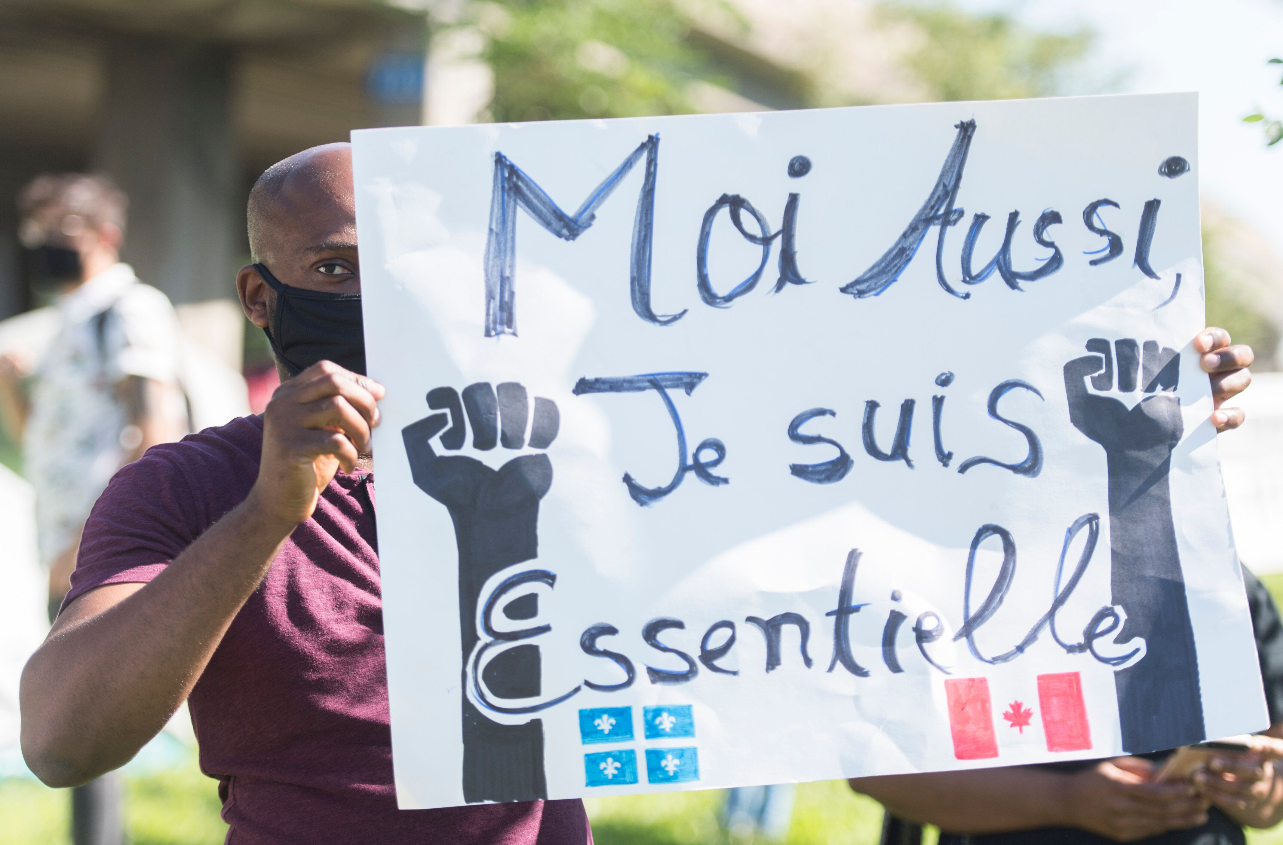 People take part in a protest outside Prime Minister Justin Trudeau's constituency office in Montreal on Aug. 15, 2020, where