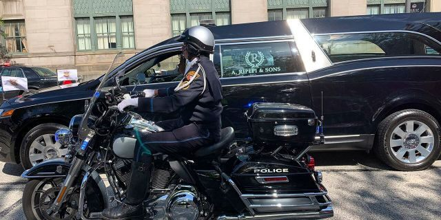 In this photo provided by the Cleveland Division of Fire, a hearse bearing the body of Detective James Skernivitz proceeds to the funeral home under police escort Saturday, Sept. 5, 2020. Skernivitz was shot and killed along with a police informant while sitting in an unmarked car during an undercover operation in Cleveland, Ohio, on Thursday, Sept. 3, 2020. (Lt. Mike Norman/Cleveland Division of Fire via AP)