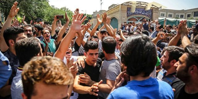 In this June 25, 2018 file photo, a group of protesters chant slogans at the main gate of the Old Grand Bazaar, in Tehran, Iran. (Iranian Labor News Agency via AP, File)