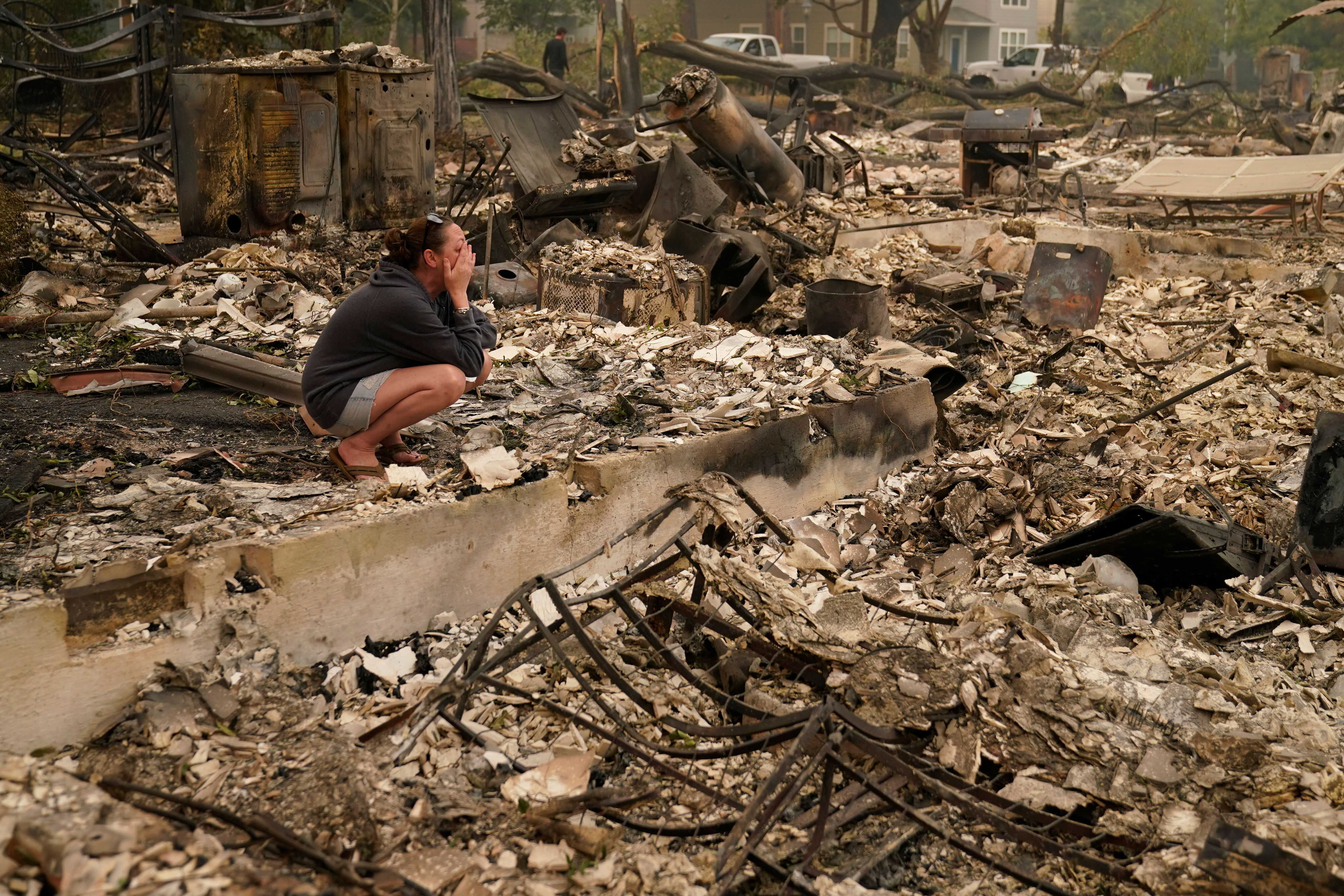 """Desiree Pierce cries as she visits her home destroyed by the Almeda Fire, Friday, Sept. 11, 2020, in Talent, Ore. """"I just nee"""