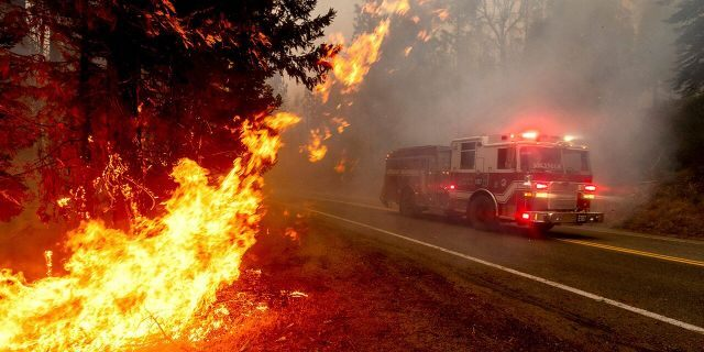 In this Sept. 7, file photo a firetruck drives along state Highway 168 while battling the Creek Fire in the Shaver Lake community of Fresno County, Calif.