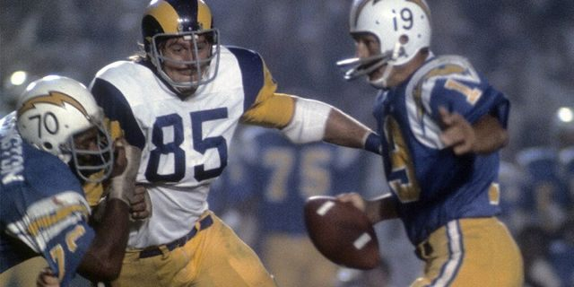 Quarterback Johnny Unitas #19 of the San Diego Charger scrambles away from defensive end Jack Youngblood #85 of the Los Angeles Rams circar 1973 during an NFL football game at Jack Murphy Stadium in San Diego, California. Unitas played for the Chargers in 1973. (Photo by Focus on Sport/Getty Images)