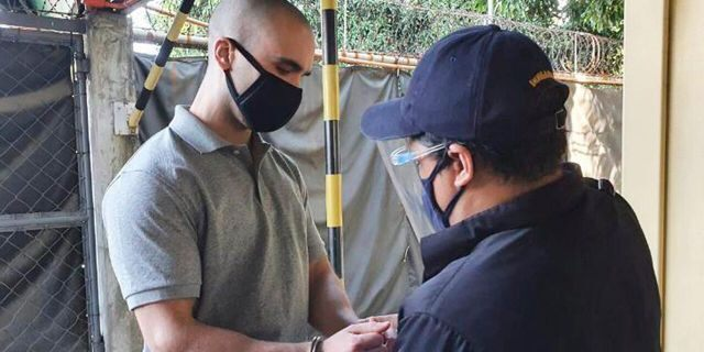 In this photo provided by the Philippines' Bureau of Immigration, U.S. Marine Lance Cpl. Joseph Scott Pemberton has handcuffs placed before leaving Camp Aguinaldo on his way to the airport in Quezon city, Philippines, Sunday, Sept. 13, 2020. (Bureau of Immigration via AP)