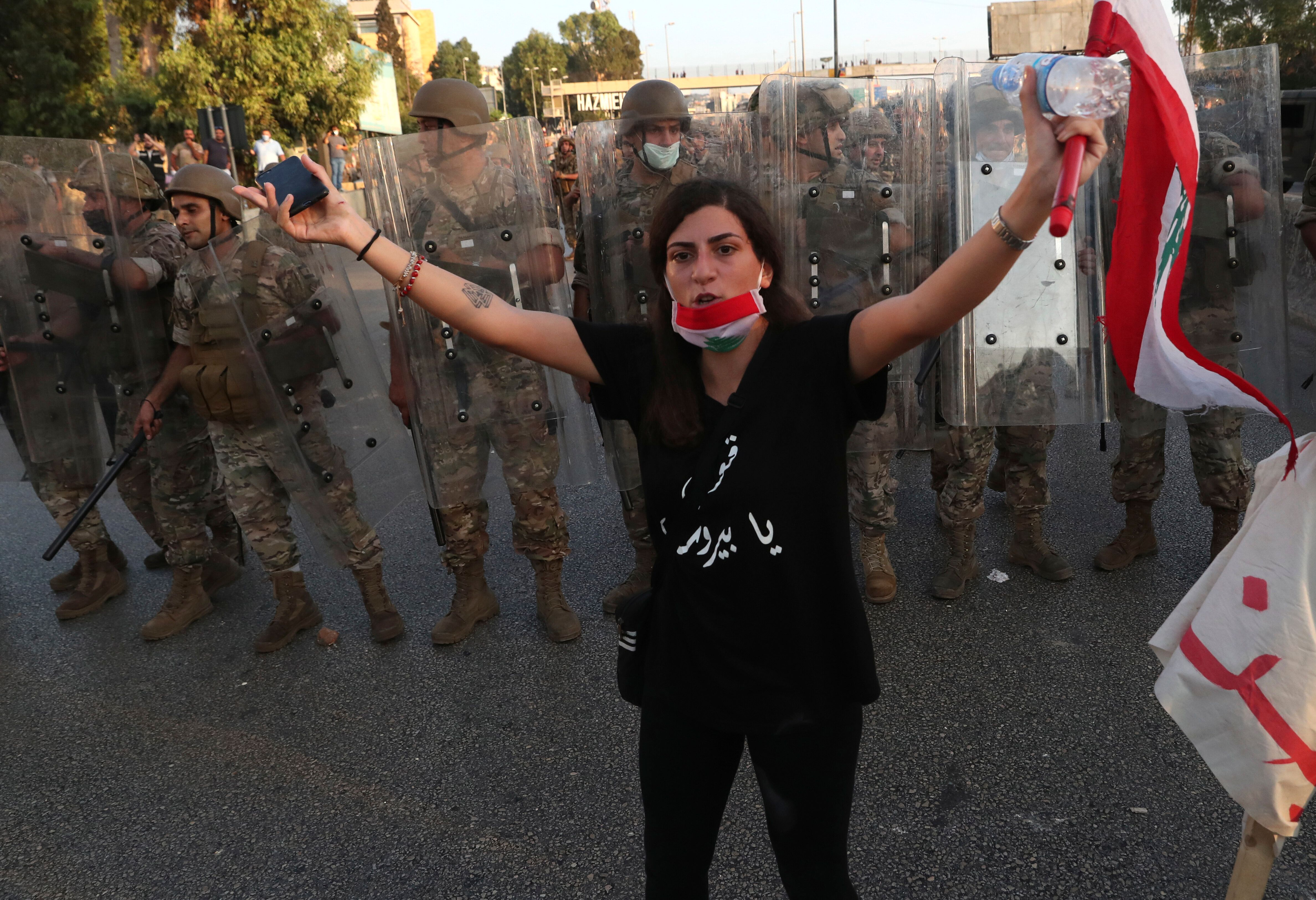 An anti-government protester tries to calm down other protesters, as she stands in front of Lebanese soldiers who bloc a road