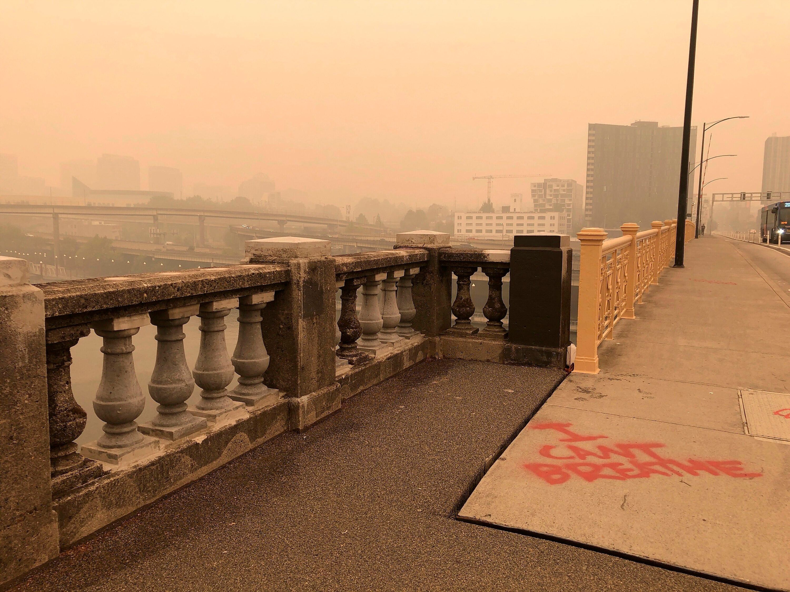 "A graffiti sign reads, ""I Can't Breathe,"" in heavy smoke from the wildfires creating an orange glow over Portland, Ore., Satu"