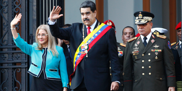 Venezuela's President Nicolas Maduro, center, and first lady Cilia Flores, wave to supporters as they leave the National Pantheon after attending a ceremony to commemorate an 1800's independence battle, in Caracas, Venezuela, Wednesday, Aug. 7, 2019. Sweeping new U.S. sanctions freeze all of the Maduro government's assets in the U.S. and even threaten to punish companies from third countries that keep doing business with his socialist administration. The first couple is accompanied by Defense Minister Gen. Padrino Lopez. (AP Photo/Leonardo Fernandez)
