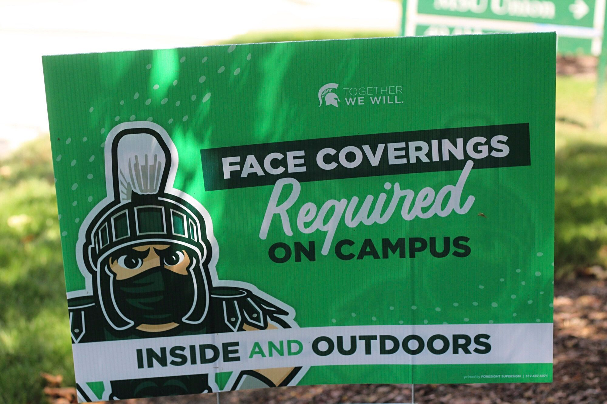 A sign outside the Michigan State University Student Union building alerts students to MSU's face covering rule on Friday. Th