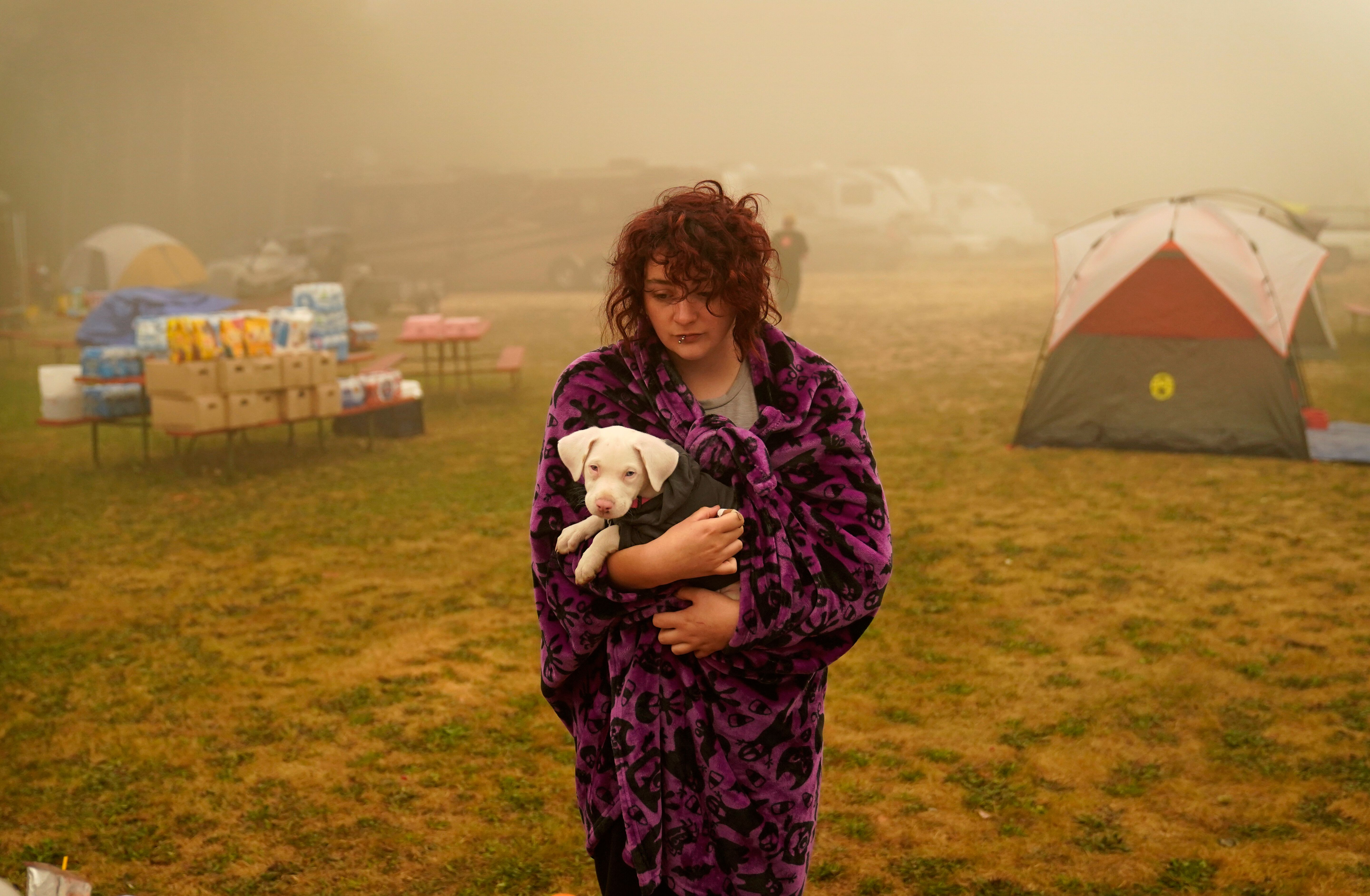 Shayanne Summers holds her dog Toph while wrapped in a blanket after several days of staying in a tent at an evacuation cente