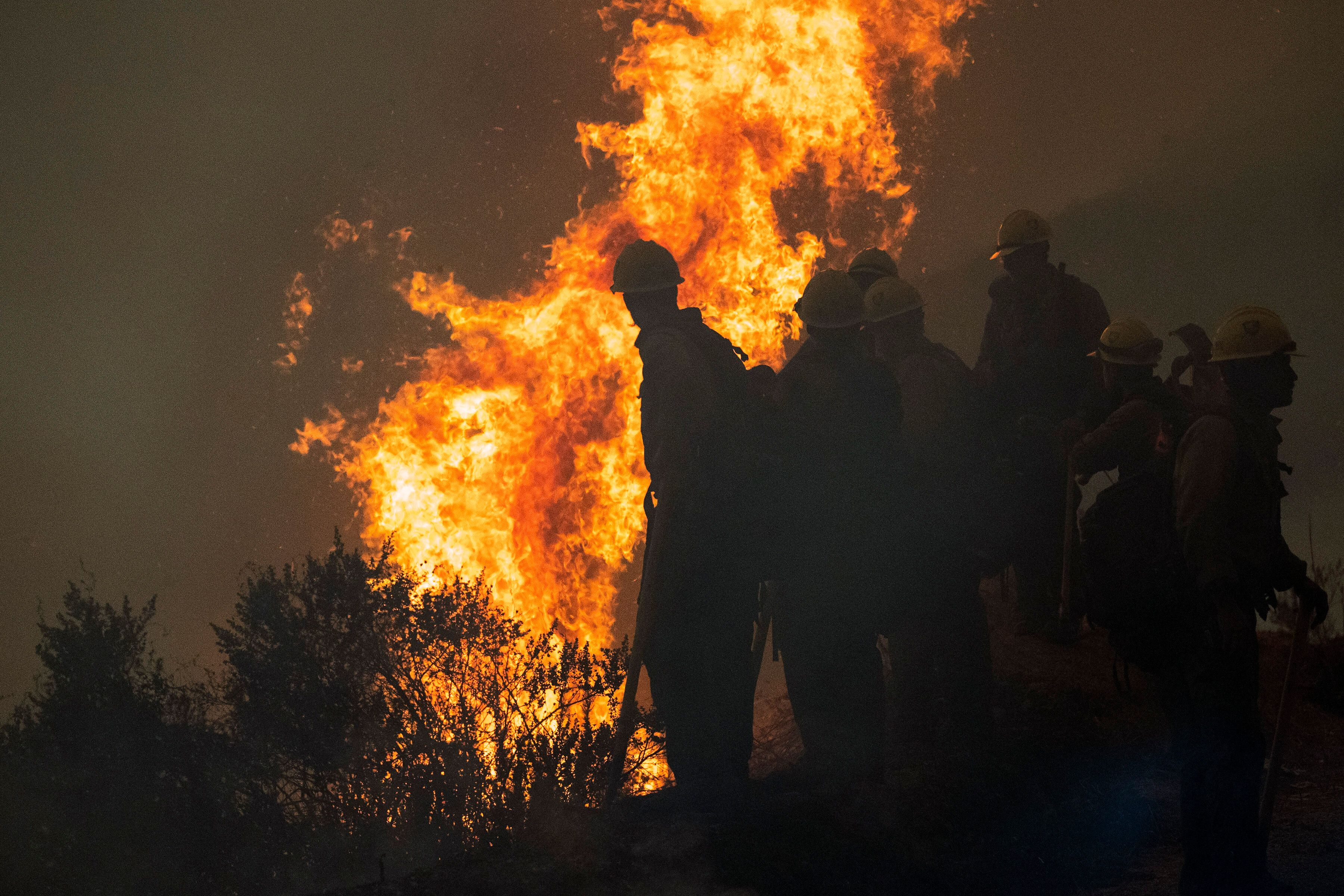 Firefighters monitor a controlled burn along Nacimiento-Fergusson Road to help contain the Dolan Fire near Big Sur, Californi