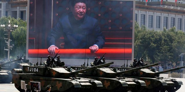 In this Thursday, Sept. 3, 2015 file photo, Chinese President Xi Jinping is displayed on a screen as Type 99A2 Chinese battle tanks take part in a parade commemorating the 70th anniversary of Japan's surrender during World War II held in front of Tiananmen Gate in Beijing. (AP Photo/Ng Han Guan, File)