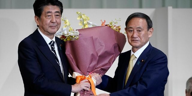 Japan's Prime Minister Shinzo Abe, left, receives flowers from Chief Cabinet Secretary Yoshihide Suga after Suga was elected as new head of Japan's ruling party at the Liberal Democratic Party's (LDP) leadership election Monday, Sept. 14, 2020, in Tokyo. The ruling LDP chooses its new leader in an internal vote to pick a successor to Prime Minister Shinzo Abe, who announced his intention to resign last month due to illness. (AP Photo/Eugene Hoshiko, Pool)