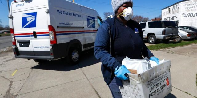 FILE: A United States Postal Service worker makes a delivery with gloves and a mask in Warren, Mich.