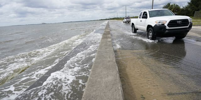 Waters from the Gulf of Mexico poor onto a local road, Monday, Sept. 14, 2020, in Waveland, Miss. (AP Photo/Gerald Herbrt)