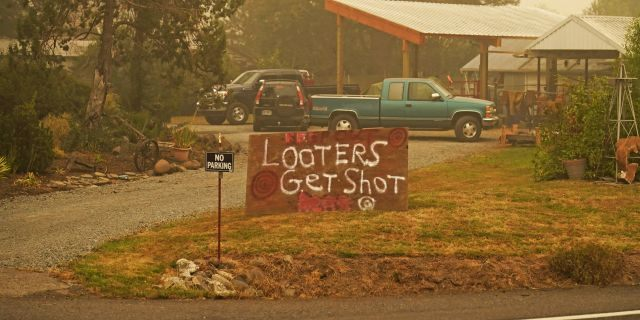 """A sign warns that """"Looters get shot"""" at a home near the Riverside Fire, Sunday, Sept. 13, 2020, near Molalla, Ore. (AP Photo/John Locher)"""