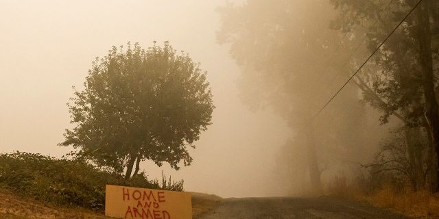 SUBLIMITY, OR - SEPTEMBER 13: A sign warns against looters as heavy smoke fills the air on September 13, 2020 in Sublimity, Oregon. Multiple wildfires grew by hundreds of thousands of acres this week forcing evacuations and road closures. (Photo by Nathan Howard/Getty Images)