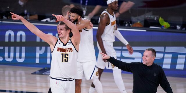 Denver Nuggets center Nikola Jokic (15) and Denver Nuggets head coach Michael Malone, right, celebrates their win over the Los Angeles Clippers in an NBA conference semifinal playoff basketball game Tuesday, Sept. 15, 2020, in Lake Buena Vista, Fla. (AP Photo/Mark J. Terrill)