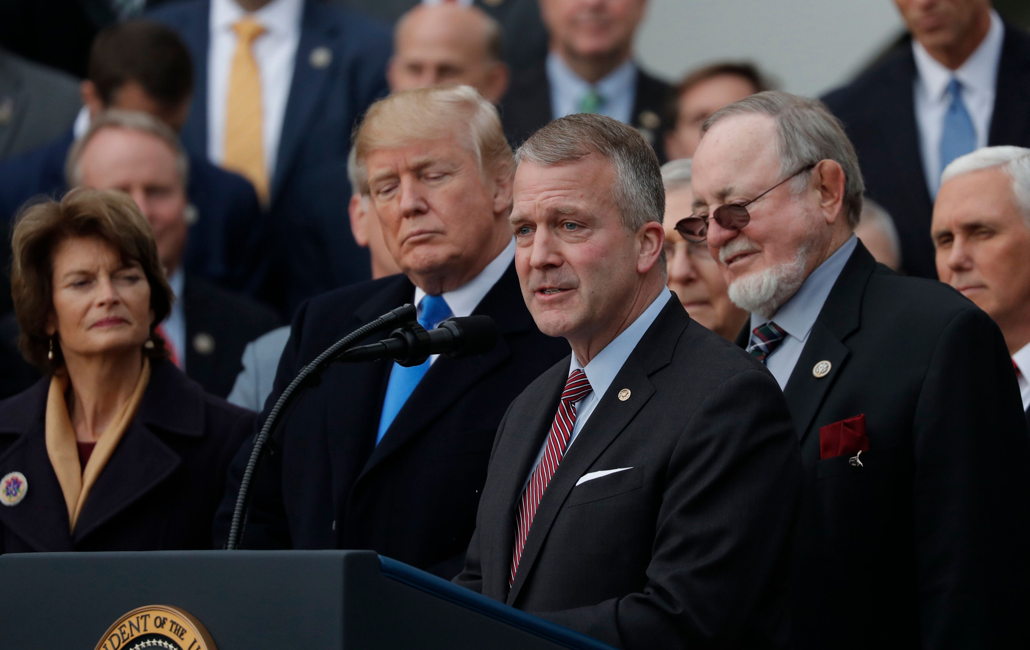 Sen. Sullivan, foreground, speaks at a ceremony celebrating Donald Trump's tax cuts. His fortunes could depend on whether Ala