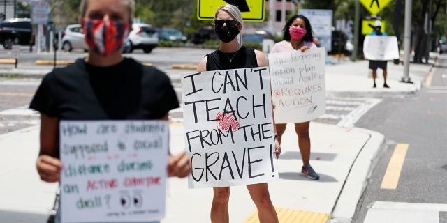 Middle school teacher Brittany Myers (center) stands in protest in front of the Hillsborough County Schools District Office on July 16, 2020, in Tampa, Fla. Teachers and administrators from Hillsborough County Schools rallied against the reopening of schools due to health and safety concerns amid the COVID-19 pandemic. (Octavio Jones/Getty Images)