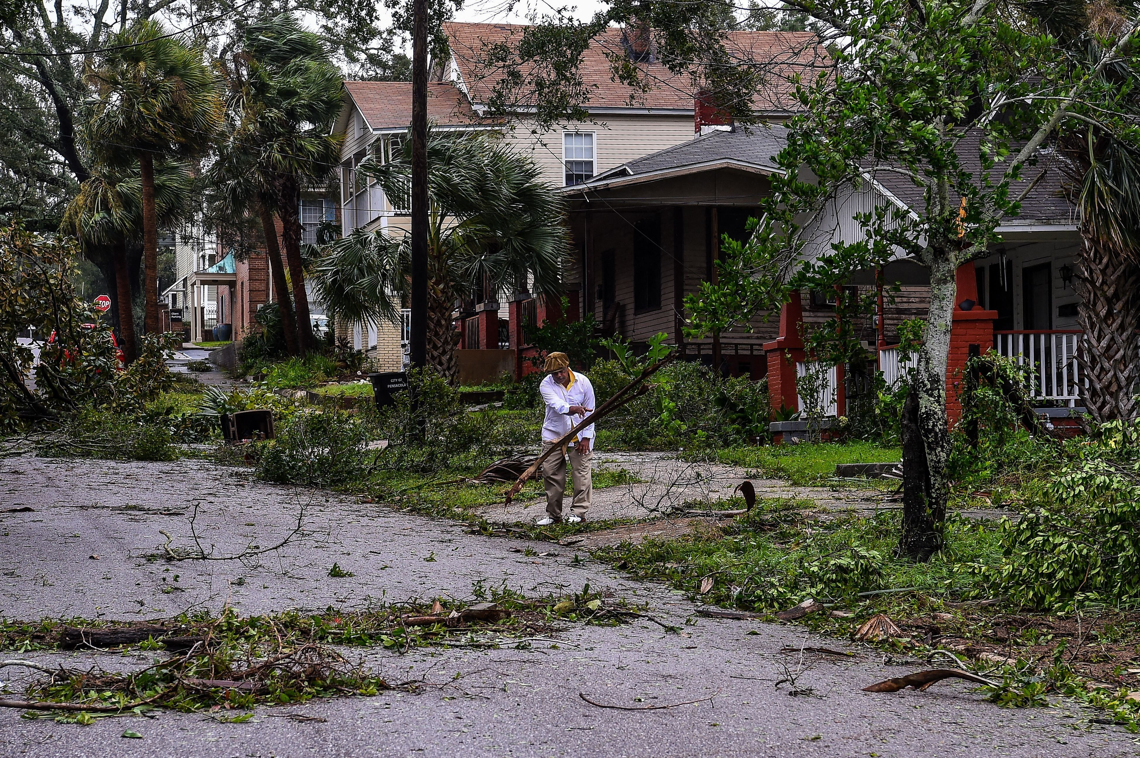 Mark Robinson removes the branch of a tree while cleaning up hurricane debris.