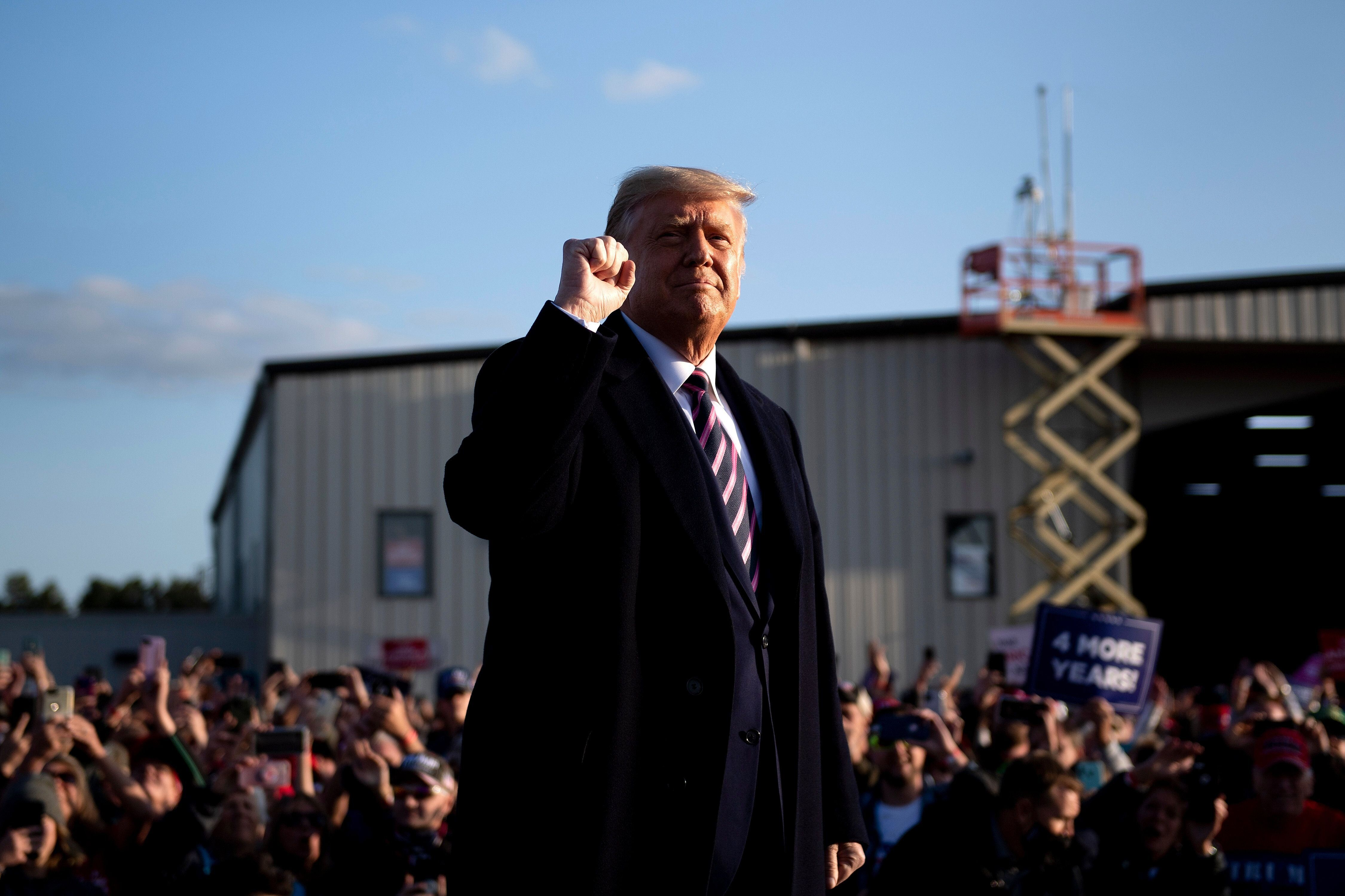 """President Donald Trump pumps his fist as he arrives for a """"Great American Comeback"""" rally Friday in Bemidji, Minnesota. Trump"""