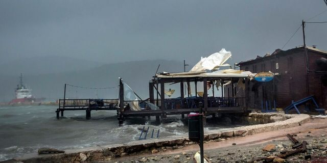Waves break on a seaside tavern during a storm at the port of Argostoli, on the Ionian island of Kefalonia, western Greece, Friday, Sept. 18, 2020.