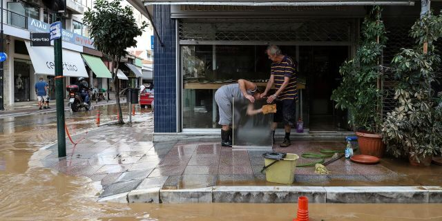 Residents clean a sheet of glass next to a flooded street after a storm at Karditsa town, Saturday, Sept. 19, 2020.