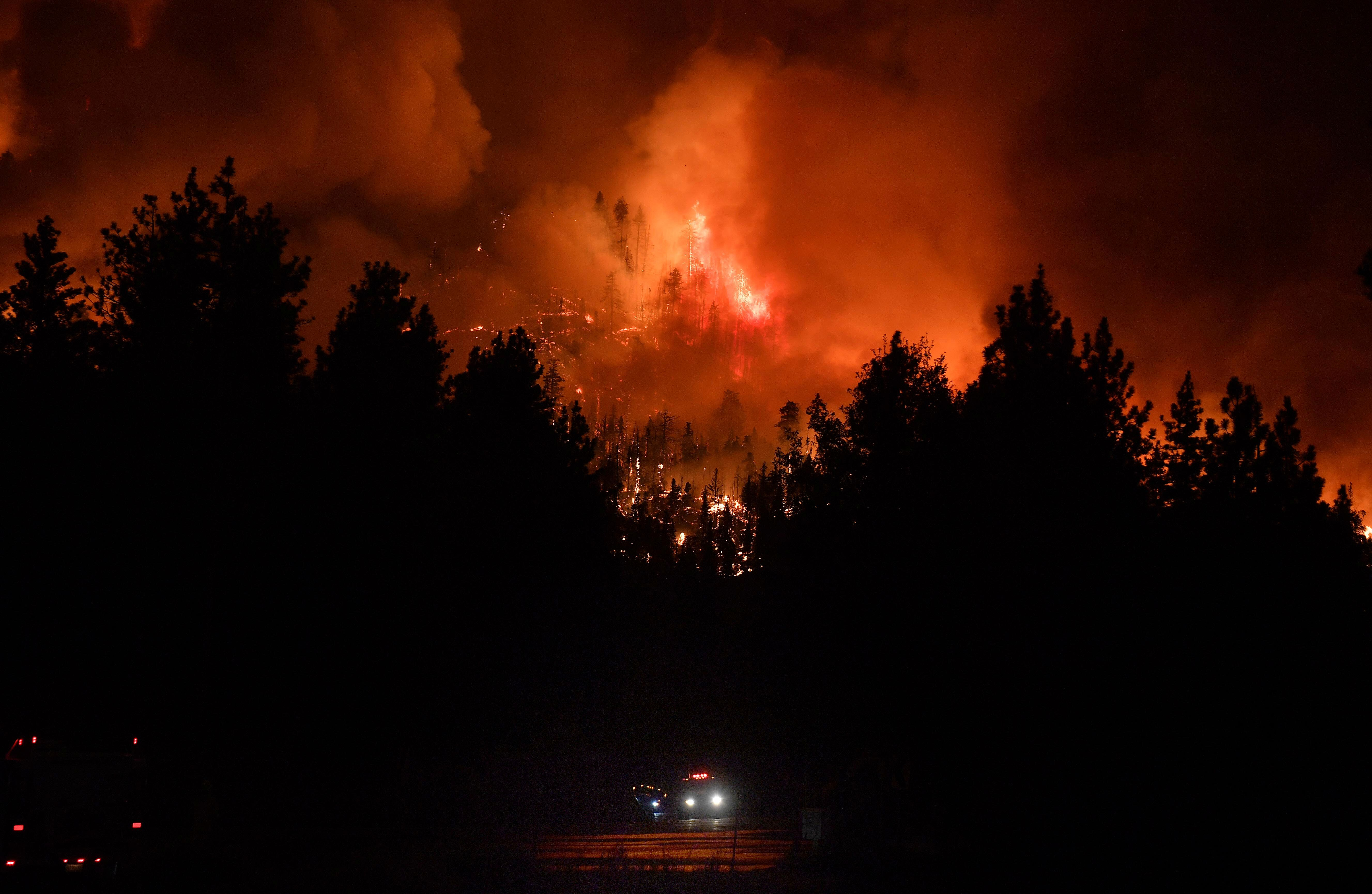 Firefighters rush up Highway 38 as the El Dorado Fire burns in heavy timber  north of Angelus Oaks, Calif., Thursday, Sept. 1